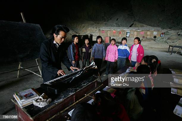 Children learn a song in music class at their school in a huge cave at a remote Miao village March 16, 2007 in Ziyun county, Guizhou province of...