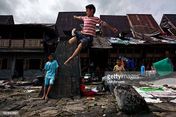 Children learns to jumping beside the stone tower in Orahili Fau village on February 20 2013 in Nias Island Indonesia Some of historians and...