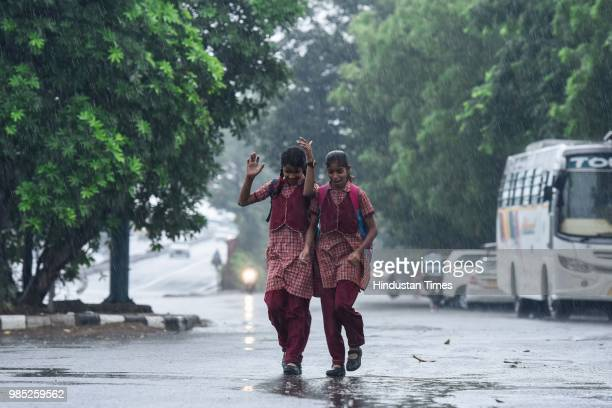 Children leave for school during the premonsoon showers near Sheikh Sarai on June 27 2018 in New Delhi India The monsoon rains are expected to arrive...