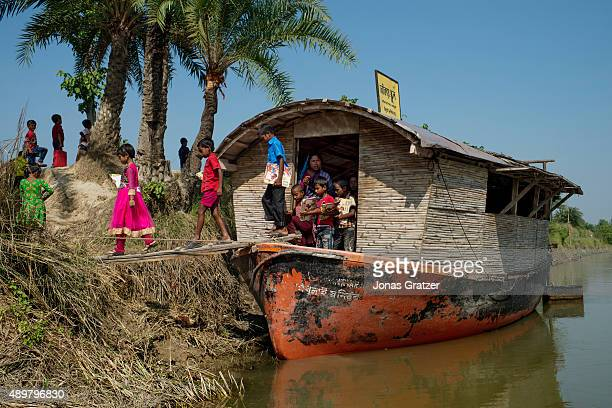 Children leave the solar powered boat school that is docked at the riverbank Shidhulai Swanirvar Sangstha has developed solarpowered floating schools...