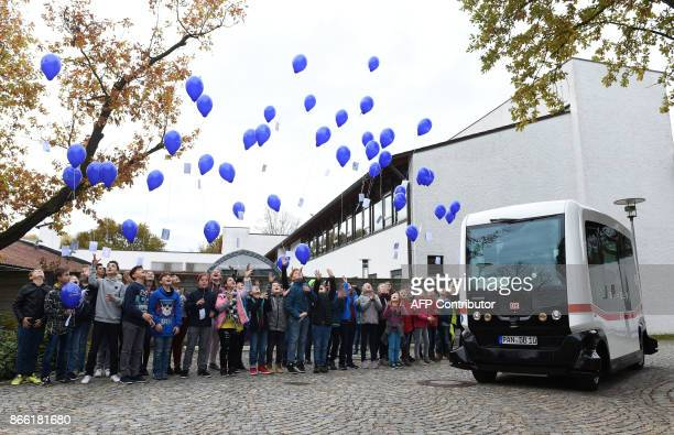 Children let balloons rise during a presentation of the first German autonomous public transport bus in Bad Birnbach southern Germany on October 25...