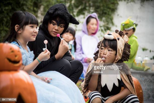 children licking candy in the yard. - halloween kids stock photos and pictures