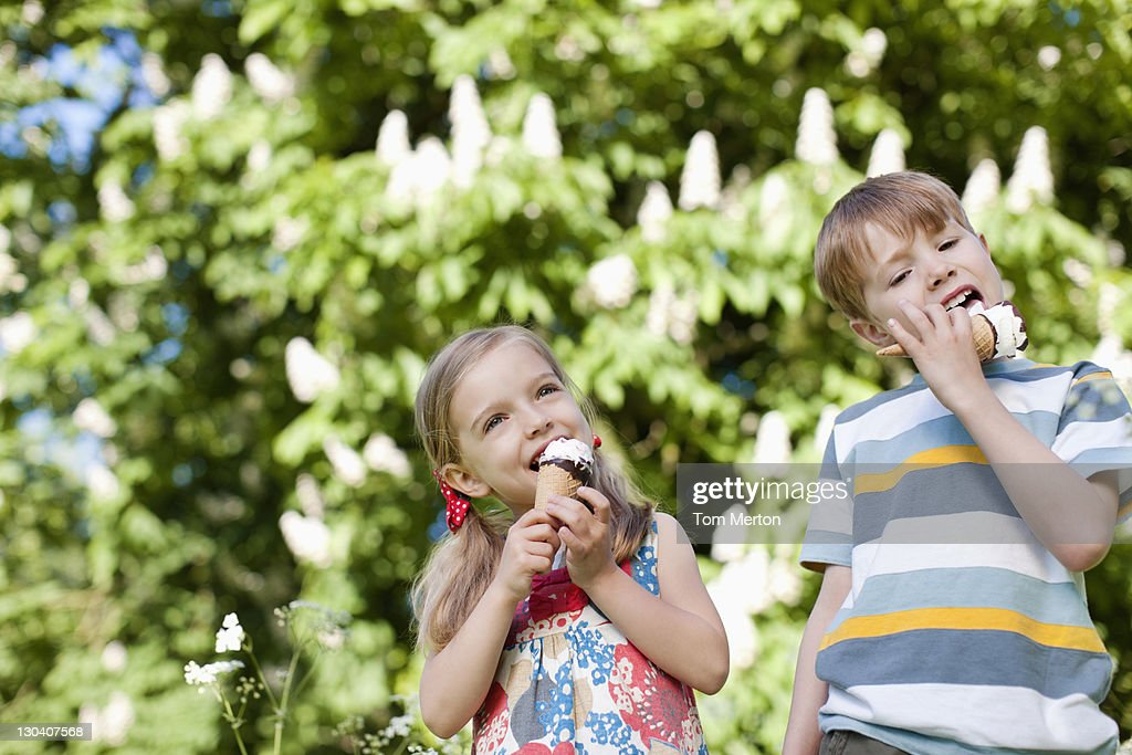 Children licking ice cream outdoors : Stock Photo