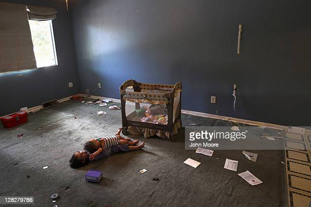 Children lie in an empty living room as an eviction team removes their family's household furniture during a home foreclosure on October 5 2011 in...