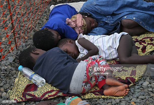Children lie on the ground before being admitted to the Doctors Without Borders Ebola treatment center after arriving by ambulance from the West...