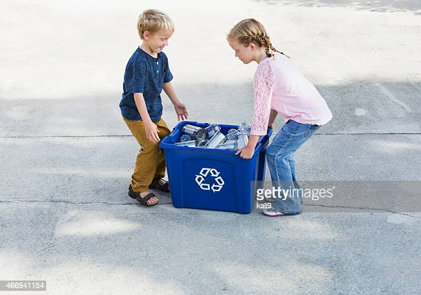 Children lifting recycling bin full of cans and bottles