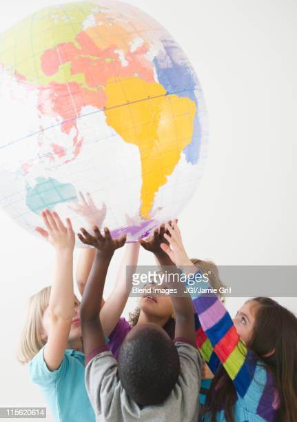 children lifting up plastic globe - responsibility stock pictures, royalty-free photos & images
