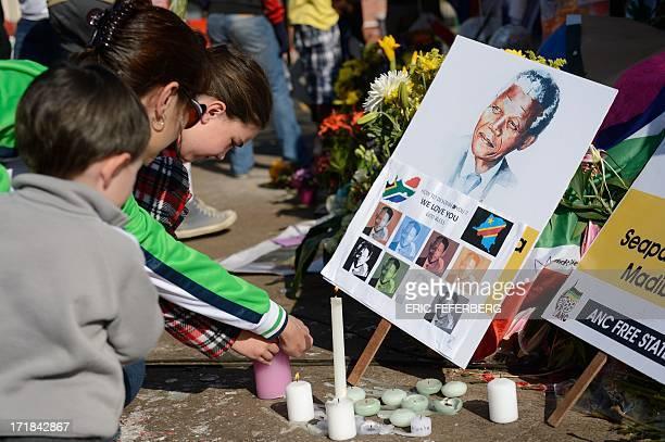 Children light candles for former South African President Nelson Mandela outside the Mediclinic Heart Hospital where Mandela is hospitalized in...
