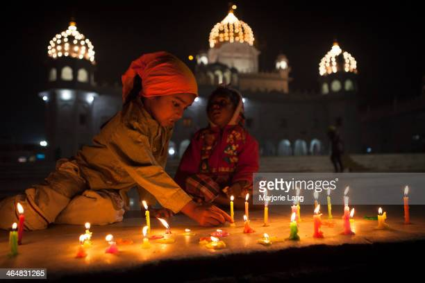 CONTENT] Children lighting candles during Diwali festival inside the Sikh Gurdwara Dukh Nivaran Sahib of Patiala Punjab India