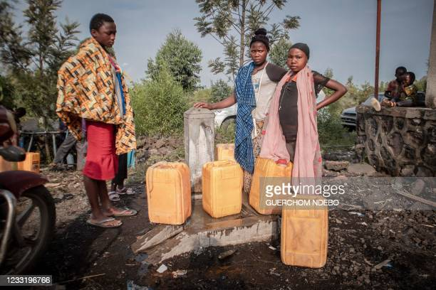 Children line up for water given to residents displaced by the volcanic eruption of Mount Nyiragongo distributed by the government in Sake, 25 km...