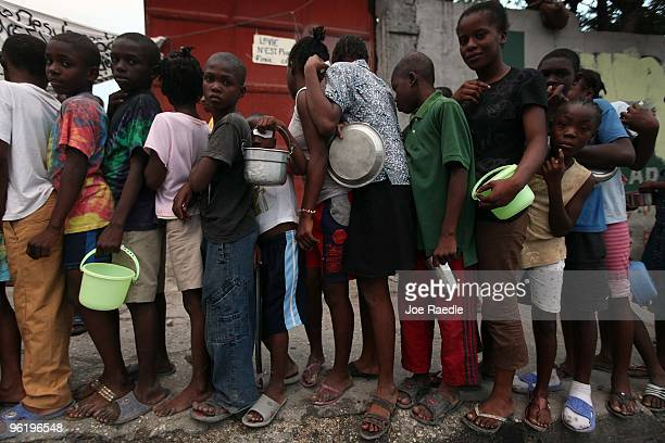 Children line up to receive food in front of the tent city that has sprung up for people who lost their homes in the massive earthquake on January...