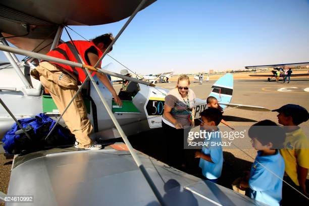 Children line up to sit inside the vintage de Havilland Tiger Moth biplane as it sits on the runway on November 20 2016 in Khartoum airport during...