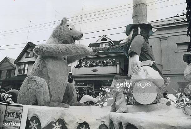 Children lining balcony of house centre watch happily as this huge bear pulls beard of an equally large elf on one of the many floats in the Santa...