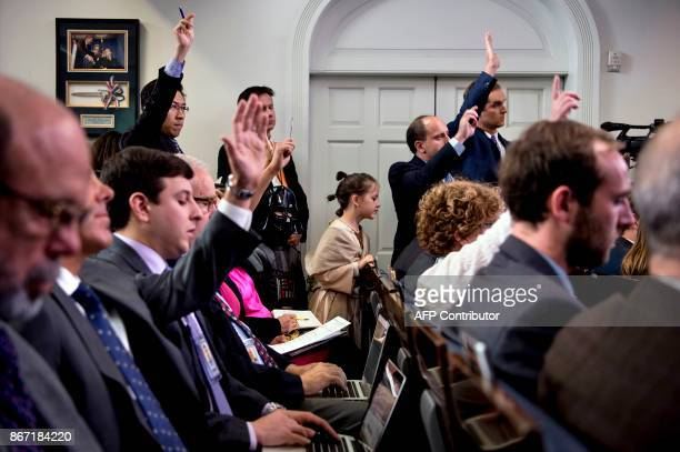 Children listen as members of the press attend a briefing at the White House in Washingotn, DC, on October 27, 2017. / AFP PHOTO / Brendan Smialowski