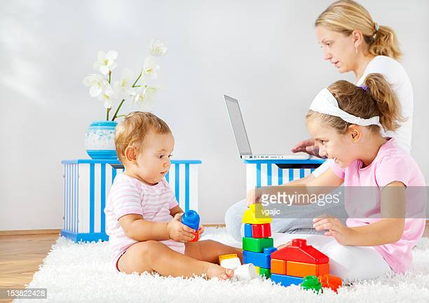 Children, little girls playing, mother working on laptop in background