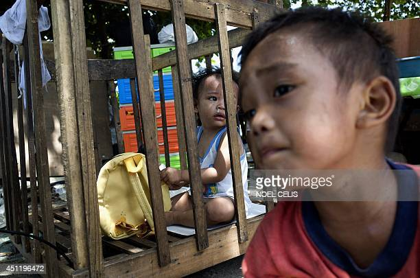 Children live a street after the demolition of a slum area left them homeless in Manila on June 25 2014 The Philippines' roaring economy cooled in...