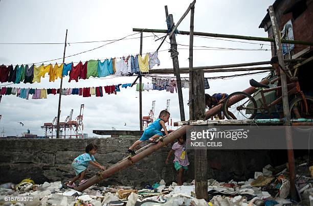 TOPSHOT Children living at shanties at the breakwater at Baseco Tondo play amongst the garbage washed ashore as a result of a storm surge of typhoon...