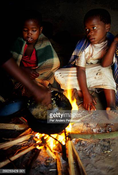 children living with hiv cooks food with a fire in their hut in naqbeni, south africa - per-anders pettersson stock pictures, royalty-free photos & images