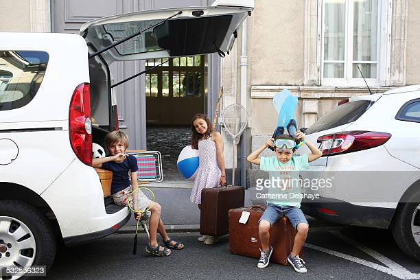 3 children loading a car before leaving on holiday - vacances photos et images de collection