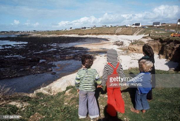 Children look at a beach covered with oil on April 12 after the sinking of the oil tanker Amoco Cadiz near the small port of Portsall on the...