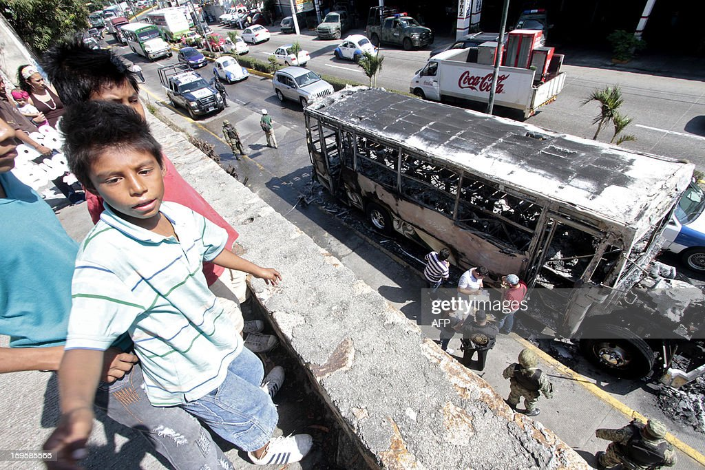 Children look at a bus after it was set ablaze in Mozimba neighborhood, Acapulco, Guerrero State, Mexico on January 16, 2013. The bus was attacked by unkown gunmen who evacuated passengers and killed the driver and his 14-year-old assistant before setting fire to the bus. AFP PHOTO/ Pedro Pardo