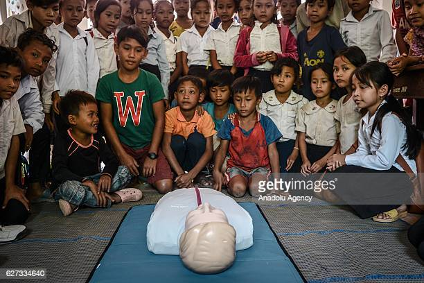 Children look at a CPR mannequin during a water safety and drowning prevention class on Monday November 28 2016 in Prey Veng province