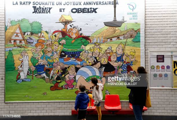 Children look at a drawing especially designed to commemorate the 60th anniversary of France's famous comic characters Asterix and Obelix as a woman...