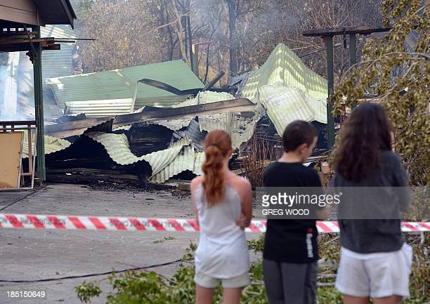 Children look at a house burnt out by bushfires in Winmalee in Sydney's Blue Mountains on October 18 2013 Residents faced scenes of devastation on...