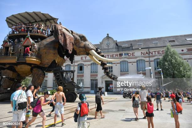 Children look at a mechanical elephant made of wood and steel at 'Les Machines de L'Ile' in Nantes western France on June 20 2017 It walks its 48ton...