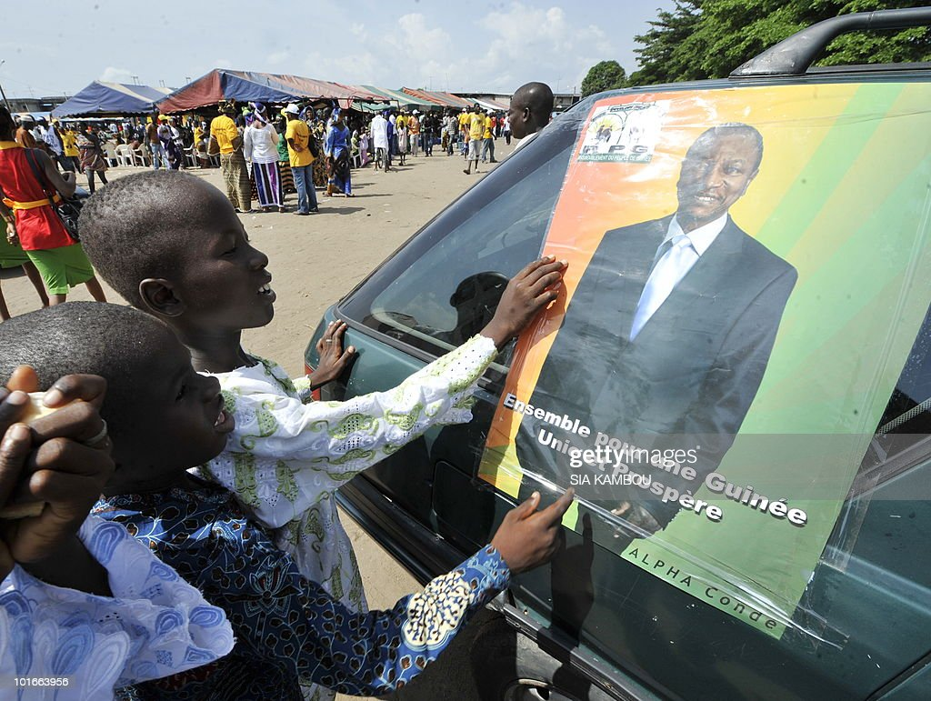 Children look at a poster of Guinean opposition leader Alpha Conde, who heads the ' Rassemblement du peuple de Guinee' (RPG) political party, in Koumassi, a popular area of Abidjan on June 6, 2010, during a political gathering of Guineans living in Ivory coast to show their support to Mr Alpha Conde ahead of the Guinean presidential election on June, 27, 2010.