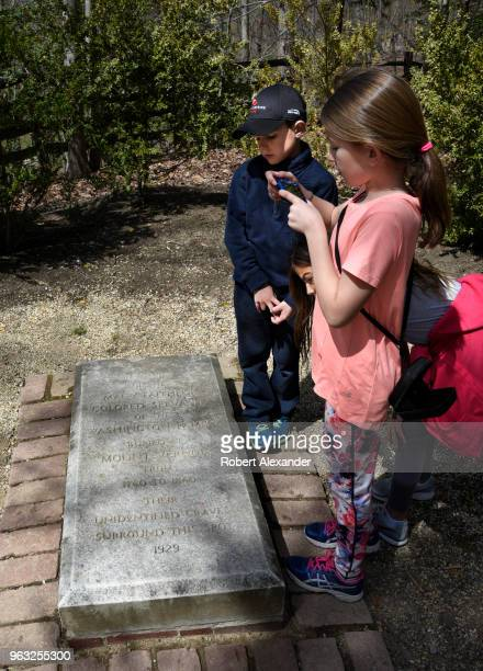 Children look at a stone marker placed near the unmarked graves of Afro Americans who served as slaves at Mount Vernon the plantation owned by George...