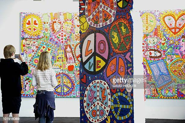 Children look at a work by US popartist James Rizzi presented in the exhibition 'Rizzi's World' on May 20 2010 in Bremen northern Germany From May 21...