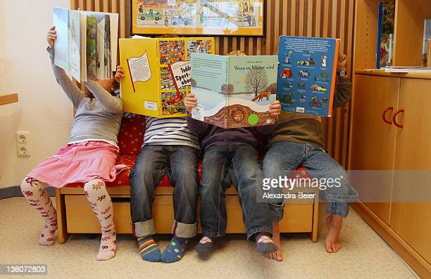 Children look at books at a day care center for children aged 12 months to six years on December 22 2011 in Munich Germany German authorities claim...