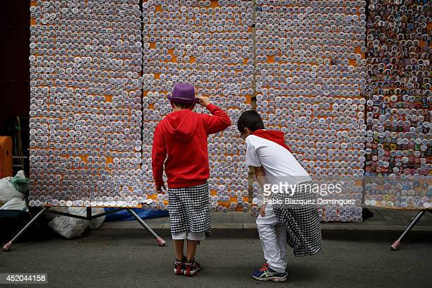 Children look at buttons sold by a street vendor during the sixth day of the San Fermin Running Of The Bulls festival on July 11 2014 in Pamplona...