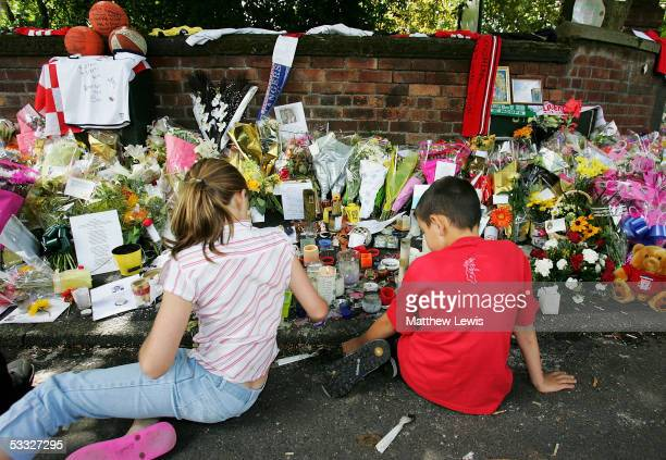 Children look at floral tributes laid at the scene where 18yearold Anthony Walker died by McGoldrick Park Huyton on August 5 2005 in Merseyside...