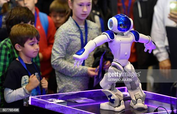 Children look at NAO a programmable humanoid robot developed by French robotics company Aldebaran Robotics during the Global Robot Expo in Madrid on...