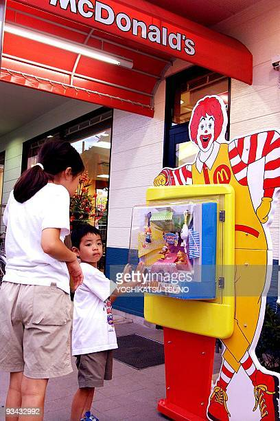 Children look at novelty goods at a McDonlad's shop in Tokyo 21 July 2001 McDonald's CO is listed on the over the counter market in Tokyo 26 July...