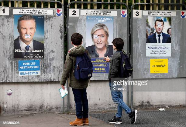 Children look at official campaign posters of Marine Le Pen French National Front and political party leader Emmanuel Macron head of the political...