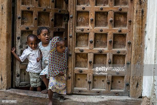 Children look at passers on a street of the Stone Town in Zanzibar City Zanzibar Tanzania on 11 October 2016