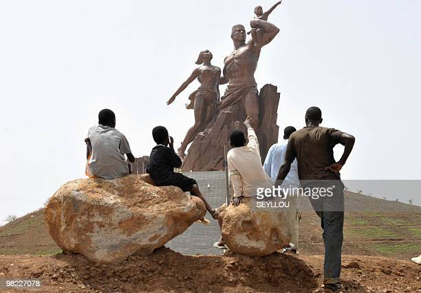 Children look at the 'African Renaissance Monument' on April 1 2010 in Dakar during preparations for the April 3 inauguration where heads of states...