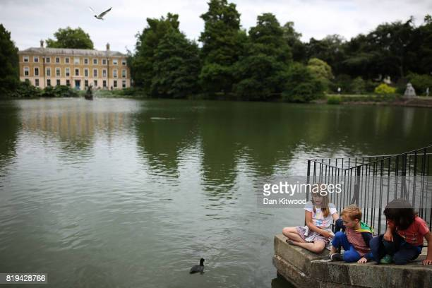 Children look at the Koi Carp in the lake at Kew Gardens on July 20 2017 in London England