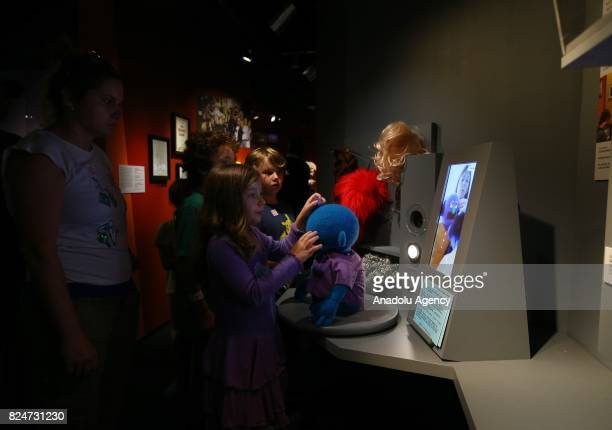 Children look at the puppets as characters of the famous TV serie Sesame Street are displayed during an exhibition in memory of American puppeteer...