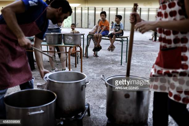 TOPSHOT Children look at volunteers cooking in the courtyard of an abandoned school used by volunteers for hosting Syrian and Afghan refugees in...