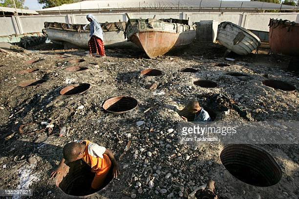 Children look for left over scraps of fish in the smoke halls at the beach October 13 2007 in Bosaso Somalia Bosaso became a place for hundreds of...