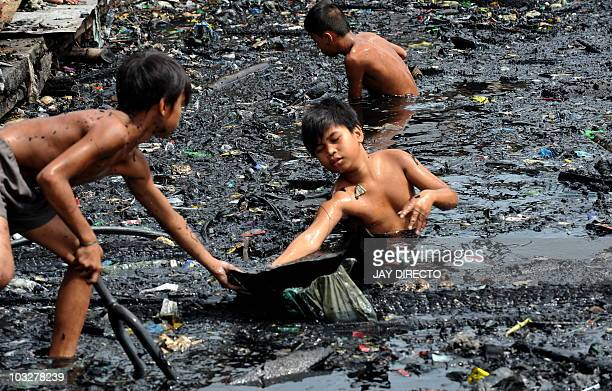 Children look for salvageable materials while submerged in water filled with charred items and ash after a fire gutted a sprawling shanty town in...