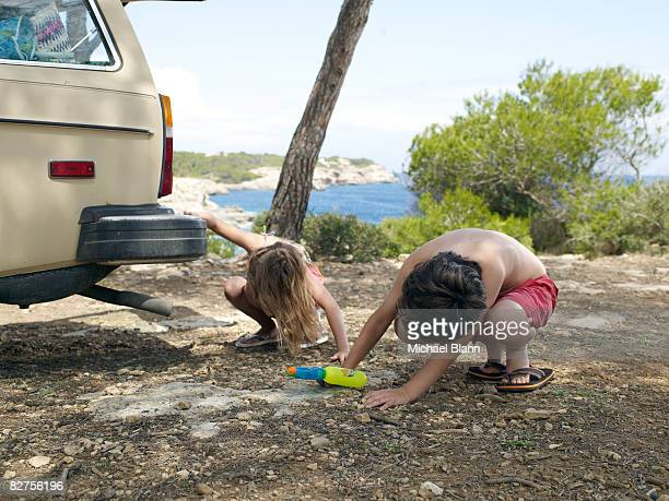 Children look for something under a car