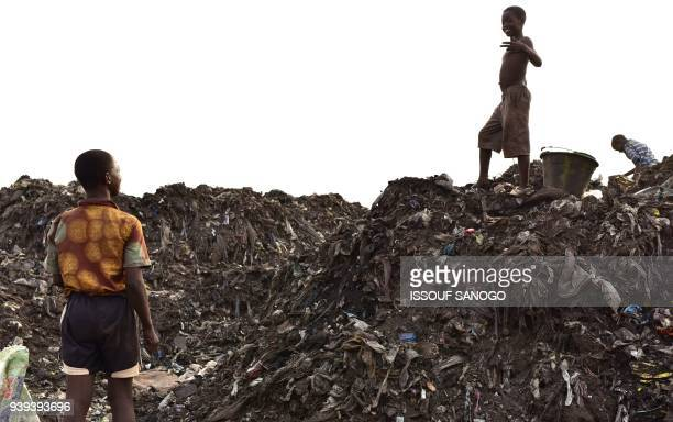 Children look for valuables in a rubbish dump in Freetown on March 28, 2018. - Sierra Leone's economy is in a dire state following the 2014-16 Ebola...