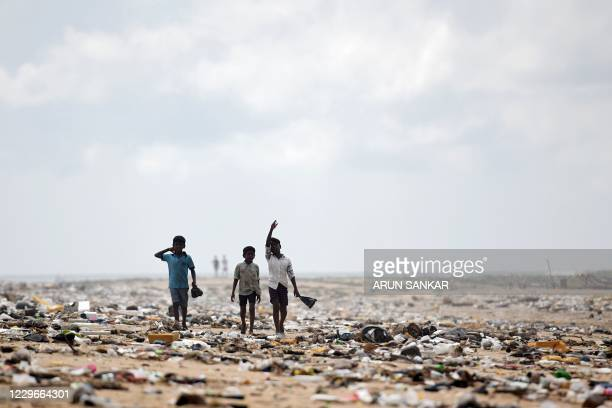 Children look for washedup plastic items from a beach after heavy rains in Chennai on November 18 2020