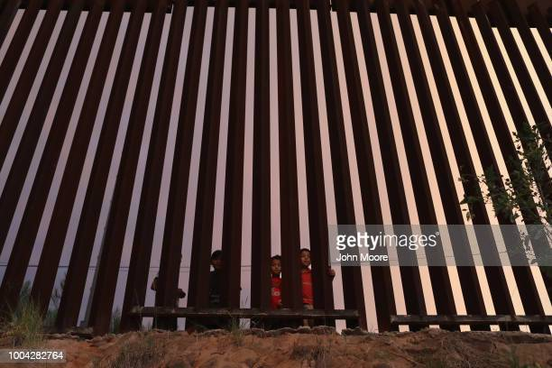 Children look from the Mexican side of the USMexico border fence at dusk on July 22 in Nogales Arizona President Trump has proposed replacing the...