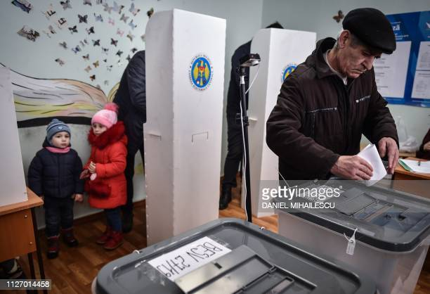 Children look on as a man casts his vote at a polling station in Chisinau on February 24 as Moldovans are called to the polls to elect new parliament...